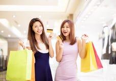Młoda kobieta pokazuje kredytową kartę i robi zakupy w centrum handlowym Fotografia Stock