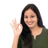 Młoda kobieta pokazuje OK znaka przeciw białemu tłu obrazy stock