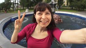 Młoda kobieta pokazuje zwycięstwo znaka robi selfie obsiadaniu fontanną w parku zdjęcie wideo