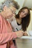 Młoda kobieta pomagać starszym osobom robi crosswords Fotografia Stock