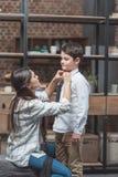 Młoda kobieta pomaga jej małego syna dostaje ubierającą i wiąże krawat zdjęcia royalty free