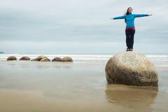 Młoda kobieta pozuje na górze jeden Moeraki głazu, Nowa Zelandia Zdjęcia Stock