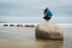 Młoda kobieta pozuje na górze jeden Moeraki głazu, Nowa Zelandia Zdjęcie Stock