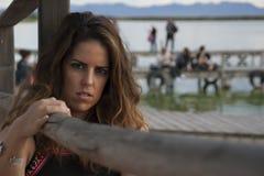 Młoda kobieta pozuje patrzejący kamery obsiadanie obok drewnianego poręcza zdjęcie stock