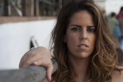 Młoda kobieta pozuje patrzejący kamery obsiadanie obok drewnianego poręcza obrazy royalty free