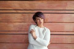 Młoda kobieta pozuje przy drewnianą ścianą Obrazy Royalty Free