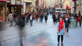 Młoda kobieta pozuje, ruchliwa ulica, ludzie chodzi wokoło, HD zbiory