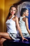Młoda kobieta pozuje siedzieć obok lustra Obrazy Royalty Free