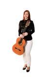 Młoda kobieta pozuje w pracownianym mieniu klasyczną gitarę Zdjęcie Royalty Free