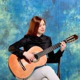 Młoda kobieta pozuje w pracownianym mieniu klasyczną gitarę Obraz Stock