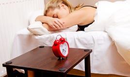Młoda kobieta próbuje spać gdy budzika dzwonienie Obrazy Royalty Free