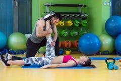 Młoda kobieta pracująca z osobistym trenerem przy gym out obrazy royalty free