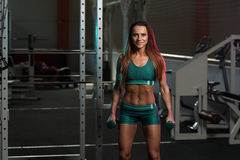 Młoda Kobieta Pracujący bicepsy Z Dumbbells Out zdjęcia royalty free