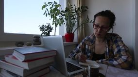 Młoda kobieta pracuje na laptopie podczas gdy siedzący w domu zdjęcie wideo