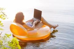 Młoda kobieta pracuje na laptopie w wodzie na nadmuchiwanym ri fotografia royalty free