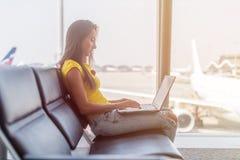 Młoda kobieta pracuje na laptopu obsiadaniu w wyjściowym holu lotnisko Obrazy Royalty Free