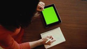 Młoda kobieta pracuje na pastylka komputerze przy kawiarnią zielony ekran zbiory
