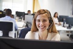 Młoda kobieta pracuje przy komputerem z słuchawki w ruchliwie biurze zdjęcia stock