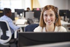 Młoda kobieta pracuje przy komputerem z słuchawki w ruchliwie biurze fotografia stock