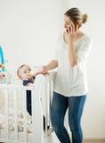 Młoda kobieta pracuje w domu i opowiada telefonem podczas gdy karmiący h fotografia stock