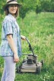 Młoda kobieta pracuje w ogrodowej arymaż trawie z gazonu kosiarzem Obrazy Royalty Free
