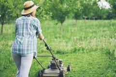 Młoda kobieta pracuje w ogrodowej arymaż trawie z gazonu kosiarzem Zdjęcie Stock