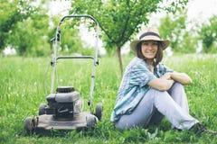 Młoda kobieta pracuje w ogrodowej arymaż trawie z gazonu kosiarzem Zdjęcia Stock