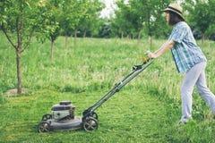 Młoda kobieta pracuje w ogrodowej arymaż trawie z gazonu kosiarzem Fotografia Stock