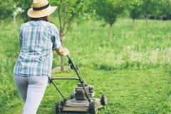 Młoda kobieta pracuje w ogrodowej arymaż trawie z gazonu kosiarzem Fotografia Royalty Free