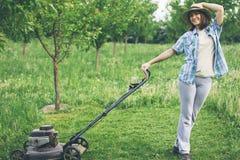 Młoda kobieta pracuje w ogrodowej arymaż trawie z gazonu kosiarzem Obrazy Stock