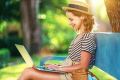 Młoda kobieta pracuje z laptopem na naturze w lecie w parku obraz royalty free