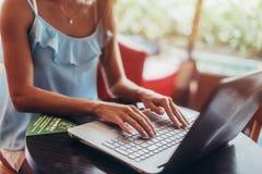 Młoda kobieta pracuje z laptopu obsiadaniem przy kawiarnią obraz stock