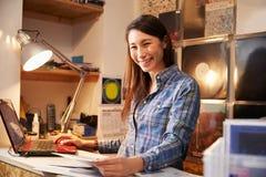 Młoda kobieta pracuje za kontuarem przy dokumentacyjnym sklepem Obraz Stock