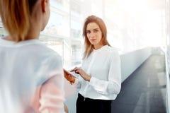 Młoda kobieta prawnik używa dotyka ochraniacza dla konsultuje jej nowego klienta podczas gdy one stoi w nowożytnym wnętrzu, Zdjęcia Stock