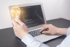 Młoda kobieta programisty ręki mienia żarówka, kobieta wręcza cyfrowanie i programowanie na parawanowym laptopie, nowi pomysły z  obraz royalty free