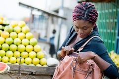 Młoda kobieta przed stosem pomarańcze, patrzeje w torebce zdjęcia stock
