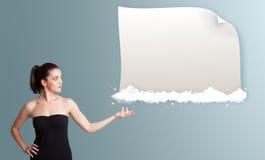Młoda kobieta przedstawia nowożytną kopii przestrzeń na chmurach obraz stock
