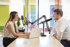 Młoda kobieta przeprowadza wywiad gościa w studiu dla podcast zdjęcia stock