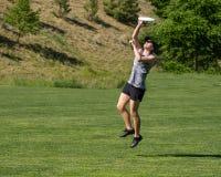 Młoda kobieta przeskakuje dla latającego dyska obrazy stock