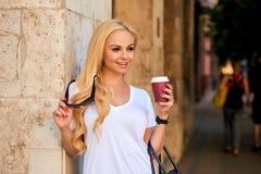 Młoda kobieta przy ścianą na ulicie z kawą zdjęcia stock
