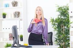 Młoda kobieta przy biurem trzyma czerwonego klucz duży Fotografia Royalty Free