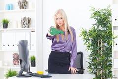 Młoda kobieta przy biurem trzyma zielonego klucz duży Obrazy Royalty Free