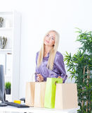 Młoda kobieta przy biurem z pięknymi torbami Zdjęcie Royalty Free