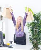 Młoda kobieta przy biurem z pięknymi torbami Obrazy Royalty Free