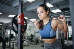 Młoda kobieta przy gym używać sprawności fizycznej wyposażenie Zdjęcie Royalty Free