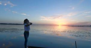 Młoda kobieta przy molem rzeką przy zmierzchem zdjęcie wideo