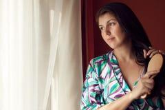 Młoda kobieta przy okno szczotkuje włosy Zdjęcia Stock