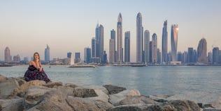 Młoda kobieta przy zmierzchem z Dubaj Marina przy tłem Zdjęcie Stock