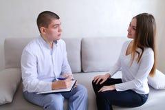 Młoda kobieta przychodził widzieć doktorskiego faceta który słucha i pisze Facet a Zdjęcie Stock