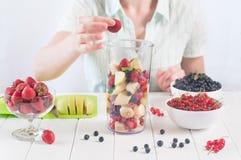 Młoda kobieta przygotowywa mieszać owoc i jagody Fotografia Royalty Free